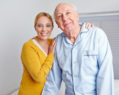 Smiling caregiver nursing senior man in family at home