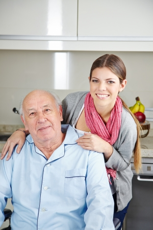 demented: Smiling young woman with a senior man in a wheelchair Stock Photo