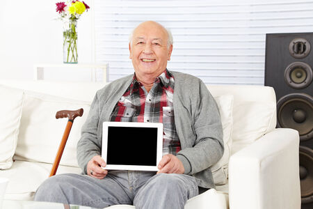Senior man holding tablet computer with empty black display photo