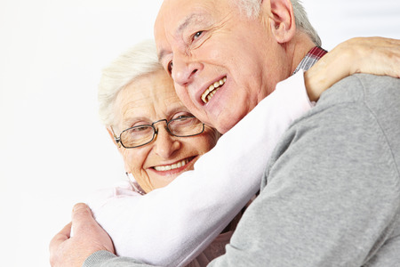 Happy senior couple embracing each other and smiling photo
