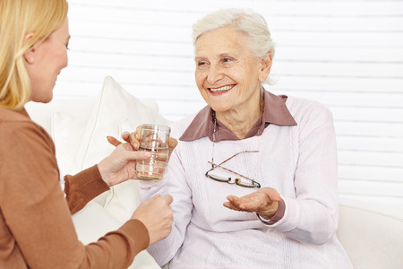 Smiling senior citizen woman taking medical pill with a cup of water photo