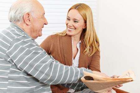vida social: Jubilado con la mujer cuidadora sonriente leyendo un periódico