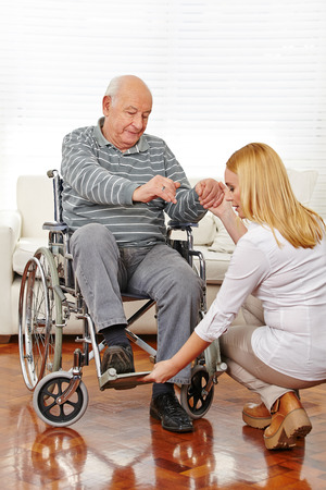Woman doing physiotherapy with senior man in wheelchair photo