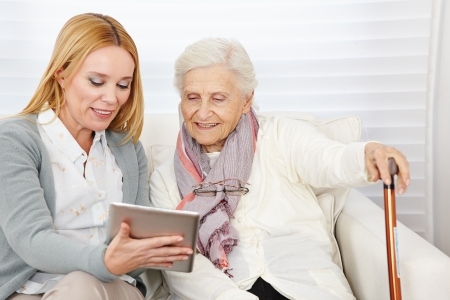 trabajo social: Mujer que da a la mujer la introducci�n de alto nivel para Internet con un equipo Tablet PC Foto de archivo