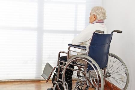 Eenzame bejaarde vrouw in een rolstoel in een verpleeghuis