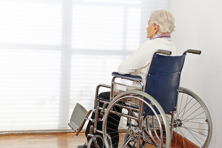 Lonely senior citizen woman in wheelchair in a nursing home photo