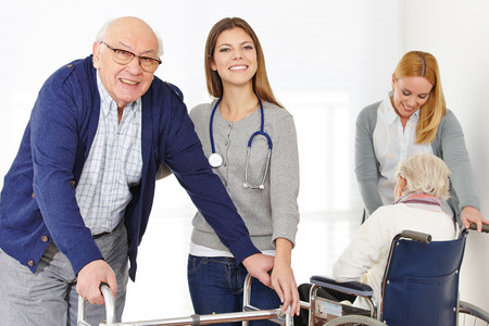 rehab: Nursing service with two women for senior couple at home Stock Photo