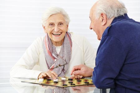 jugar: Feliz pareja de ancianos jugando a las damas en una casa de retiro