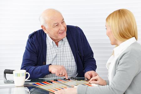 spielen: Frau spielt Backgammon mit Senioren in einem Altersheim