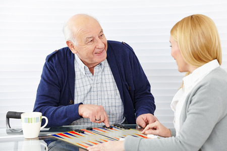 backgammon: Woman playing backgammon with senior citizen in a retirement home
