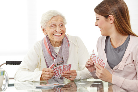 social work aged care: Happy senior woman playing cards with caregiver at home Stock Photo