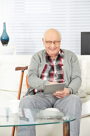 social apartment: Senior man using tablet computer at home in the living room