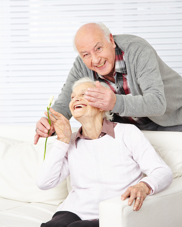 surprising: Senior man surprising his happy woman with some Freesia flowers