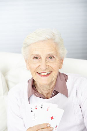 Smiling senior woman holding four aces in her hand while playing cards photo