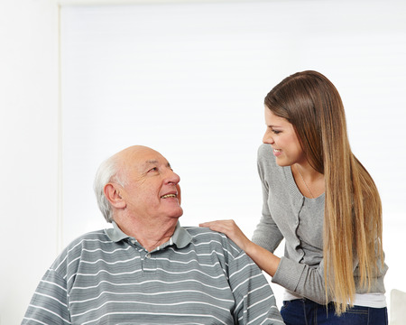 social work aged care: Granddaughter and happy grandfather smiling at each other Stock Photo