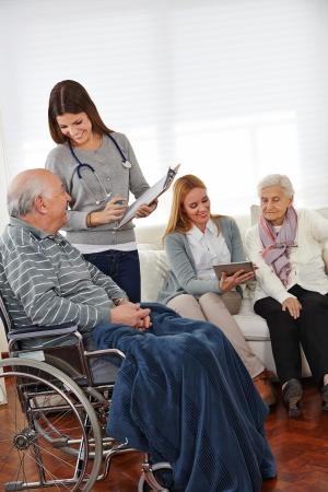 pielęgniarki: Kobiety w służbie opieki robi badania pod seniorów z schowka i tablet