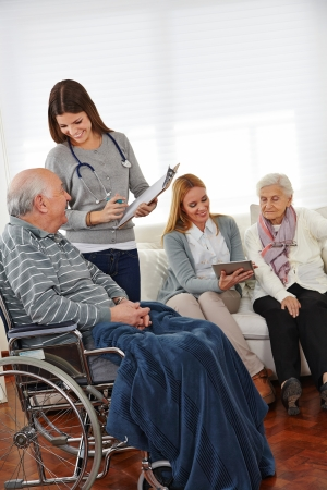 enfermeria: Las mujeres en el servicio de enfermer�a haciendo los reconocimientos previstos en la tercera edad con portapapeles y Tablet PC Foto de archivo