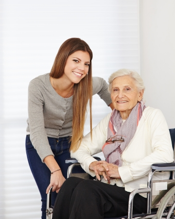 social work aged care: Young woman and happy senior citizen in a wheelchair