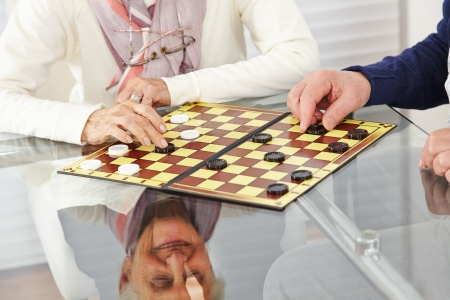 social apartment: Happy senior citizen couple playing checkers at home