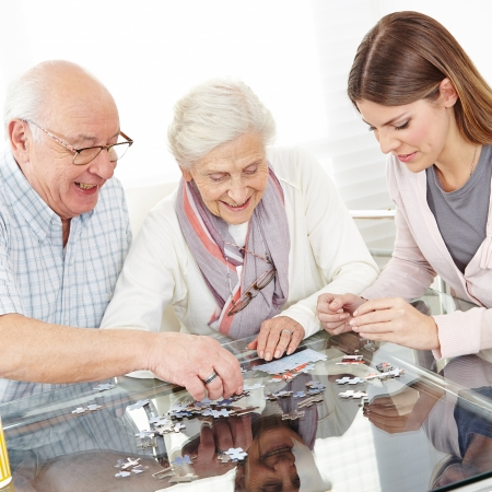 Senior couple solving jigsaw puzzle together with family at home