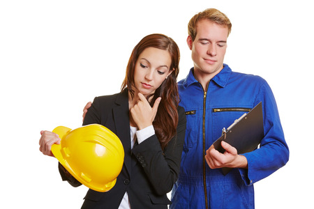 role reversal: Career change with worker and businesswoman exchanging helmet and clipboard Stock Photo