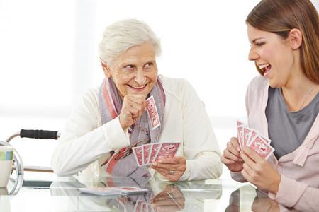 Gelukkig senior vrouw speelkaarten met ouderenzorg verpleegkundige