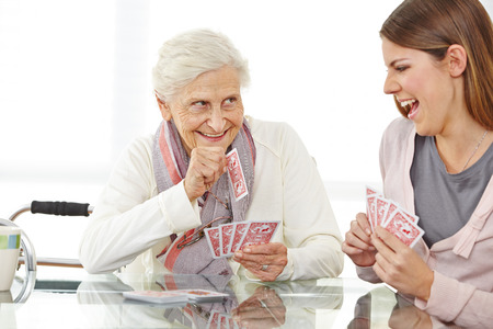 senior citizens: Happy senior woman playing cards with eldercare nurse Stock Photo