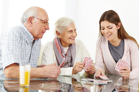 card game: Happy family with senior couple playing cards at home