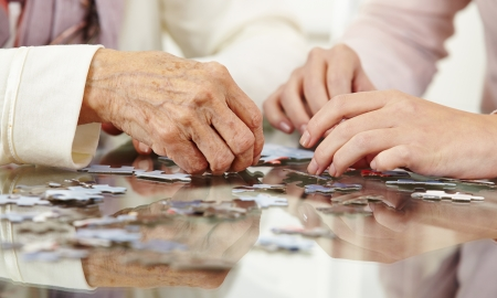 rehab: Old hands solving jigsaw puzzle in a nursing home Stock Photo