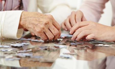 persona de la tercera edad: Viejas manos para resolver rompecabezas en un hogar de ancianos