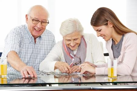 Un giovane assistente sociale risolvere puzzle con coppia senior a casa Archivio Fotografico