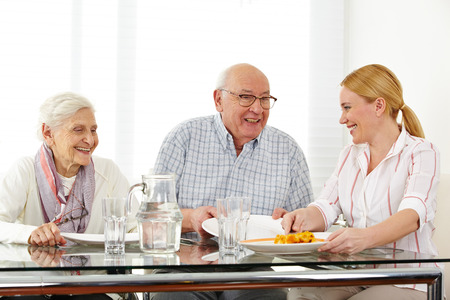 social work aged care: Happy family with senior couple eating lunch at table