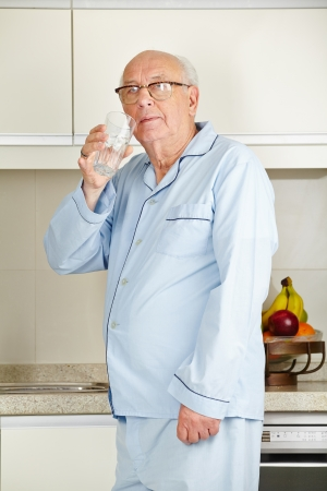 demented: Senior man in his pajamas drinking a glass of water in the kitchen Stock Photo