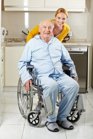 Demented senior man in wheelchair with extended care assistant photo