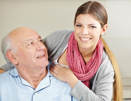 Smiling extended care assistant with happy senior citizen photo