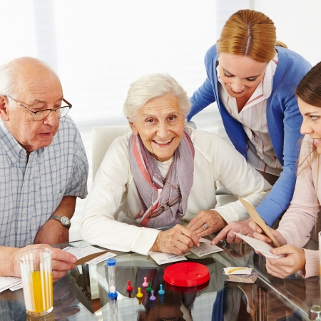 seniors homes: Happy family with senior couple playing parlor games