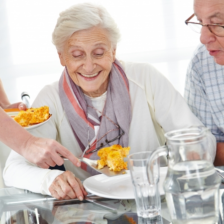 assist: Happy senior citizen couple eating lunch in nursing home