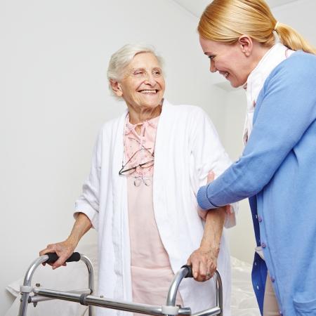Geriatrische verpleegster helpt senioren vrouw met rollator Stockfoto