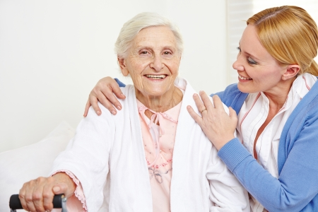 Happy senior woman getting geriatric care at home from her daughter photo