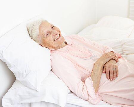 eldercare: Beddridden senior citizen woman in a nursing home smiling Stock Photo