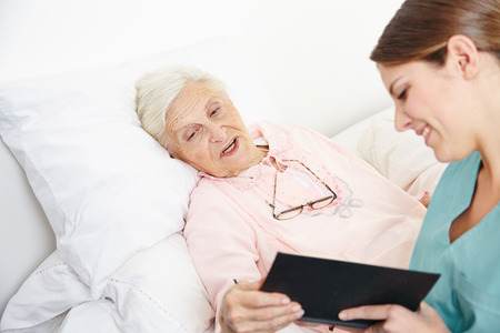 hospice: Geriatric nurse reading book to senior citizen woman in bed