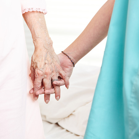 Caregiver holding wrinkly hands of senior woman at home