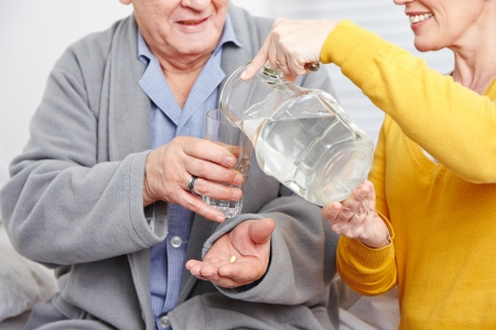 Old man at home taking a pill with glass of water photo