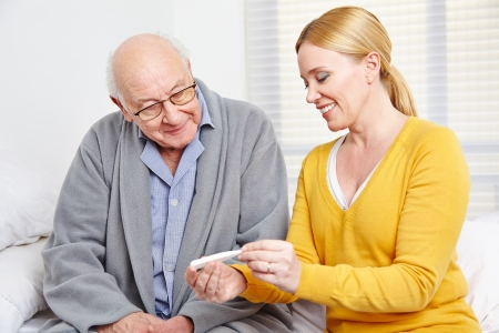 Smiling woman taking temperature of senior man with thermometer photo