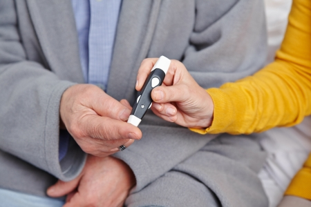 Hand of senior man with diabetes getting blood glucose monitoring photo