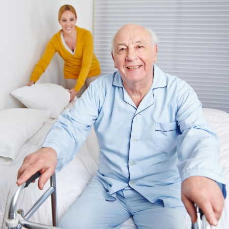 senior living: Woman fixing sheets of bed for senior citizen man in the family