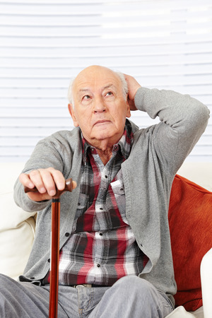 Disoriented demented old senior citizen man trying to remember photo