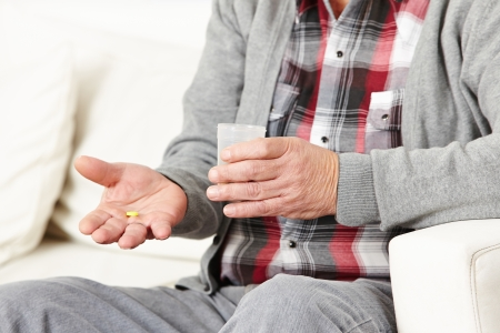 take medicine: Old man taking medical pills with a cup of water