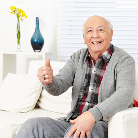 Old happy man holding thumbs up in a retirement home photo