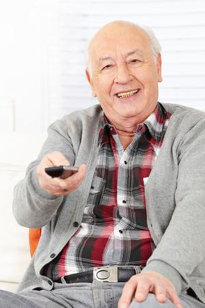 ver tv: Hombre de la tercera edad con mando a distancia viendo la televisión en casa Foto de archivo